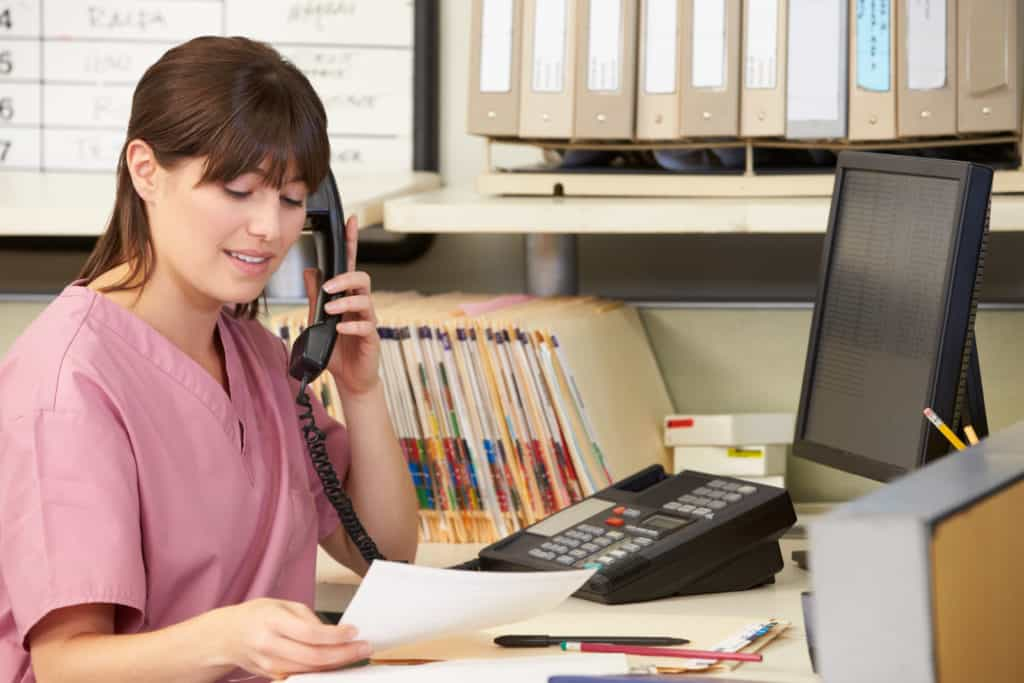 A nurse talks with a patient over the phone while reviewing records.