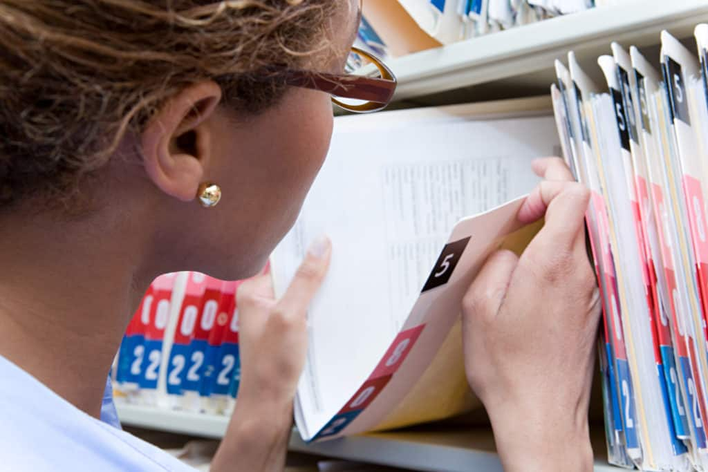 A nurse looks through a long row of patient files